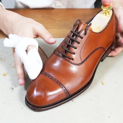 茶色い靴のつま先にハイシャインをしている画像