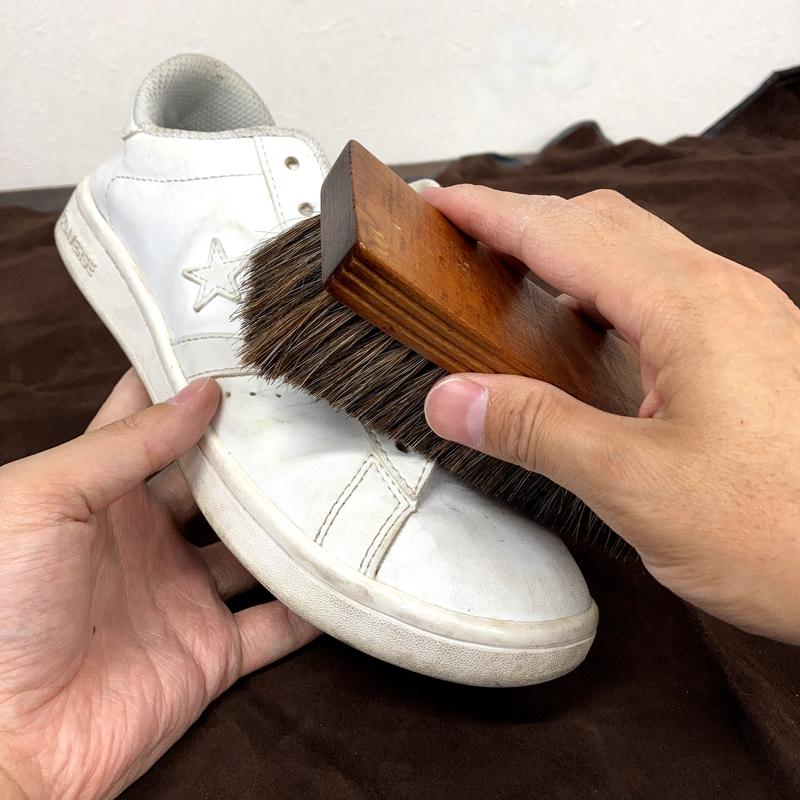 馬毛ブラシで靴についたほこりを払い落としています。