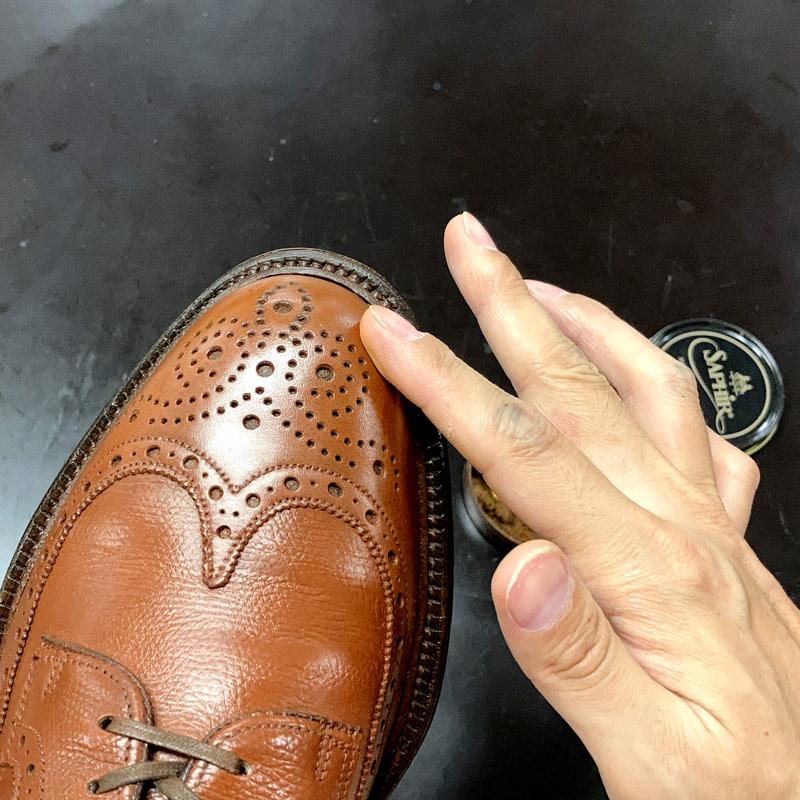 ベース色のミディアムブラウンのポリッシュを指で塗っています。